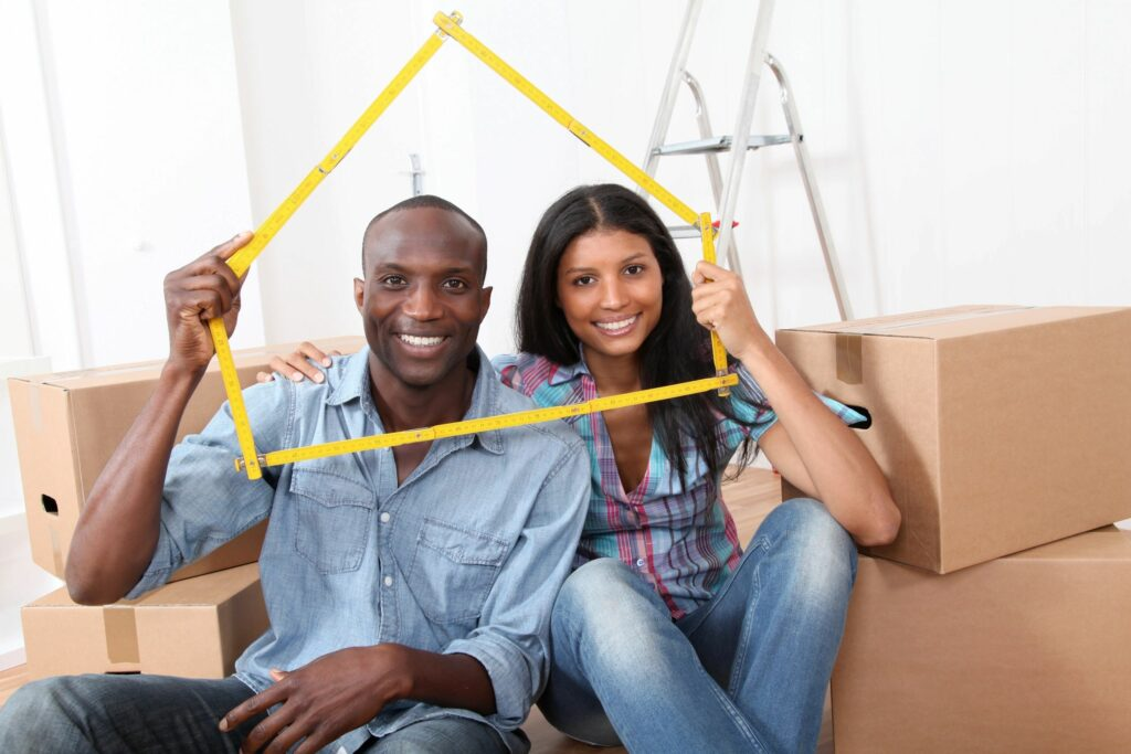 Couple posing with a measuring tape in the shape of a house