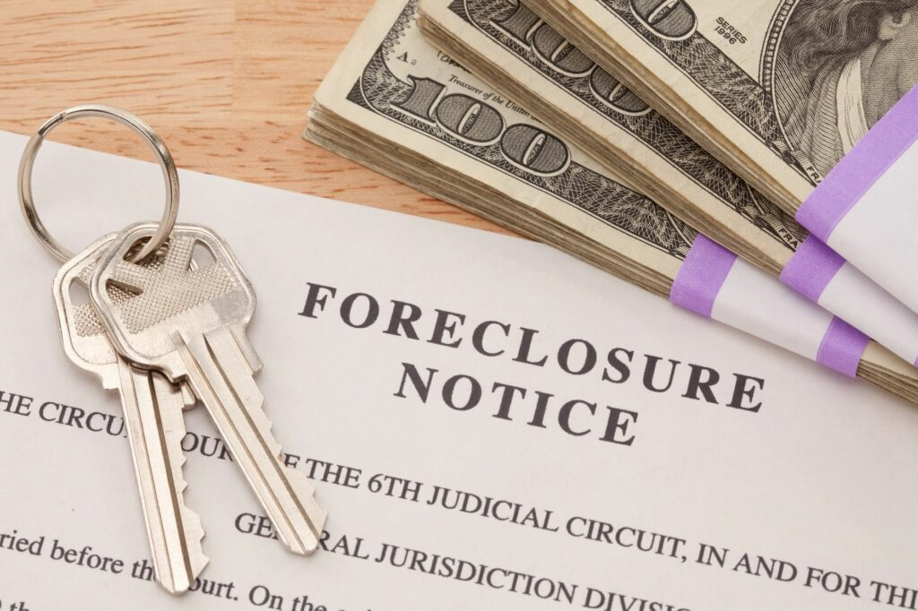 Keys and a stack of money on top of a foreclosure notice.